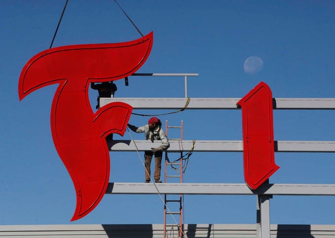 """Ruger Lewis, left, and John Vernier, connectors from Capital City Group of Columbus, position the """"F"""" in the refurbished iconic Firestone sign before attaching it as the setting moon dots the """"i"""" atop the new Bridgestone racing tire construction plant Friday in Akron."""