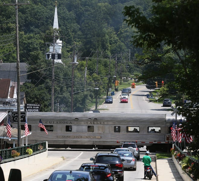 The Cuyahoga Valley Scenic Railroad train crosses State Route 303 through the heart of Peninsula, Ohio, on Wednesday, July 24, 2019. [Mike Cardew/Beacon Journal]