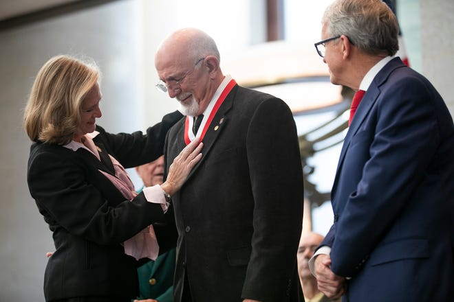 PFC Barry Smith, of Lancaster, center, receives a Hall of Fame medal, presented by Gov. Mike DeWine and Maj. General Deborah Ashenhurst, during the induction ceremony for the Ohio Military Hall of Fame for Valor class of 2021, Friday, September 24, 2021.