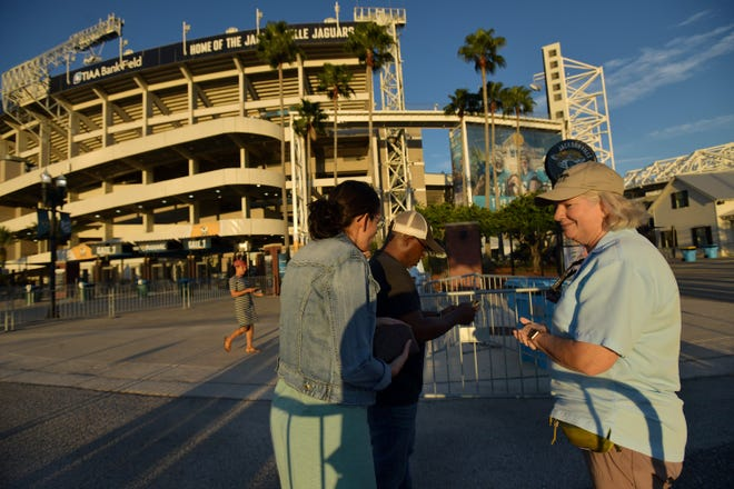 Amy Brigance with guest services waits on arriving fans to find their proof of vaccination or a recent negative COVID-19 test before they could enter the safe area for the Counting Crows concert Thursday at Daily's Place in Jacksonville.