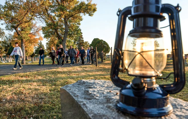Johnetta Hebrlee, left, leads a group to the next stop, marked by a latern, during a past Historic Walking Tour of Valley View Cemetery. tickets for this year's tour go on sale Sept. 27.