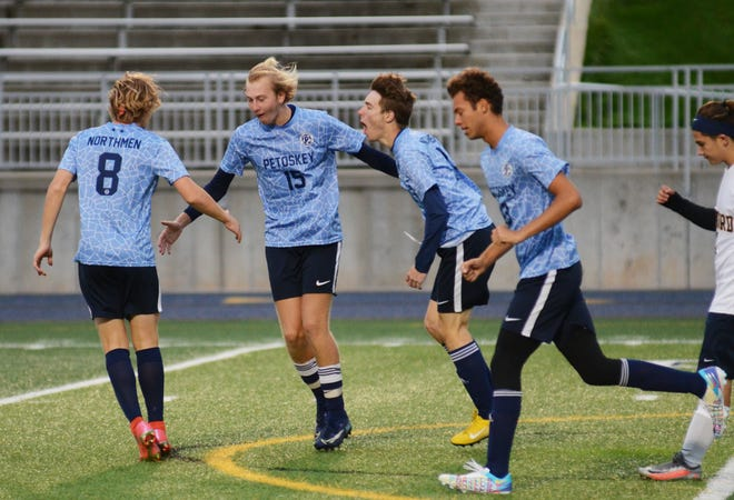 Petoskey teammates run in to celebrate with teammate Owen Ashley, who scored the Northmen's second goal against Gaylord Thursday night.