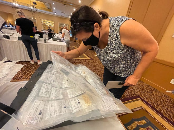Rebecca Westra, of Loxahatchee, looks at items up for bid on Sept. 24, 2021 ahead of the Florida Unclaimed Property Auction at Embassy Suites in West Palm Beach.