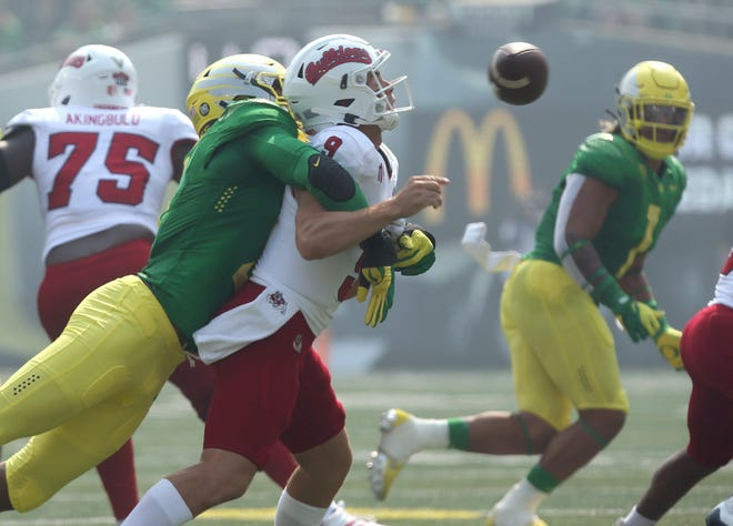Oregon's Kayvon Thibodeaux, left, sacks Fresno State quarterback Jake Haener, forcing a turnover, during the first quarter of a game earlier this month.