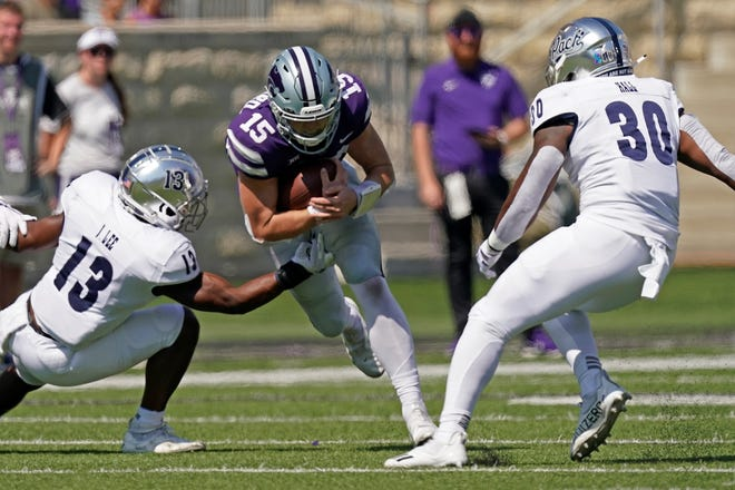Kansas State quarterback Will Howard (15) carries the ball between Nevada defensive back Jordan Lee (13) and linebacker Lawson Hall (30) during last Saturday's game in Manhattan. The Wildcats open Big 12 play at 6 p.m. Saturday at Oklahoma State.