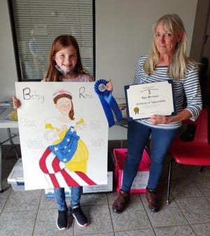 Pictured are Kyla Workman with her award-winning poster of Betsy Ross and River Mill art teacher Sharon Wilson.
