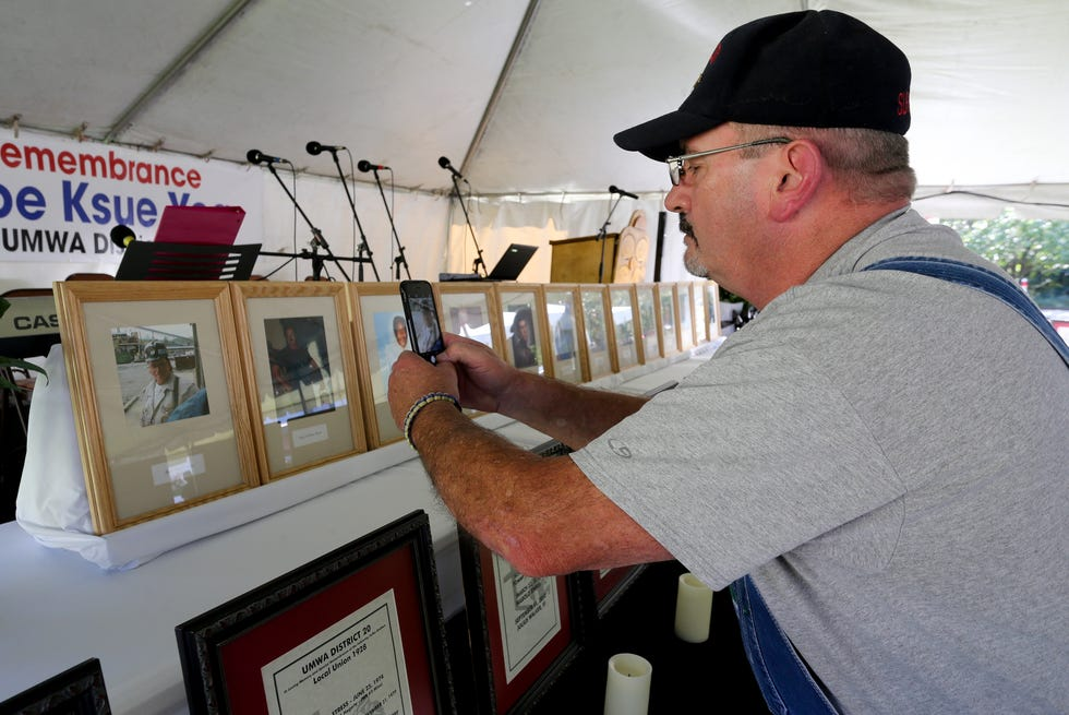 The Alabama Miners' Memorial Foundation marked 20 years since the disaster that claimed the lives of 13 coal miners at the mine in Brookwood Thursday Sept. 23, 2021. Stuart Sexton, a miner who was underground in the the mine when the explosion killed his fellow miners, takes photos of their portraits on display before the commemoration.  [Staff Photo/Gary Cosby Jr.]