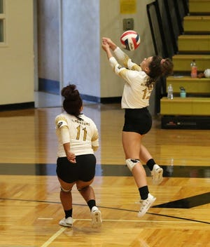 Italy's Taliyah Ezell (13) saves a ball inbounds as teammate DaNaisia McCowan (11) looks on during Tuesday night's home volleyball match against Avalon at Gladiator Coliseum.