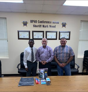 Quazeric Reed (left) poses with Rapides Parish Sheriff Mark Wood and District Attorney Phillip Terrell when he donated 12 bags of personal care items that will be given to people leaving jail after finishing their sentences.