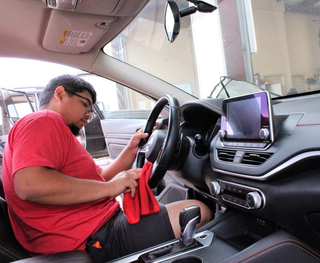 Ramiro Torres details the interior of a vehicle Friday at Abilene Auto Spa. He has been employed there for three months; the business itself recently marked its 15th anniversary.