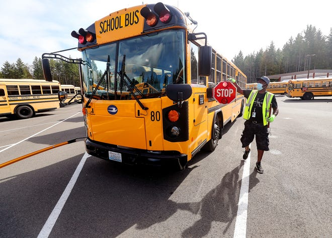 Central Kitsap School District bus driver Anthony Smith walks around his bus as he performs a safety check prior to leaving the CK School District Transportation facility in Silverdale on Thursday. Kitsap school districts are looking to hire bus drivers and substitutes as full-time in-person learning returns.