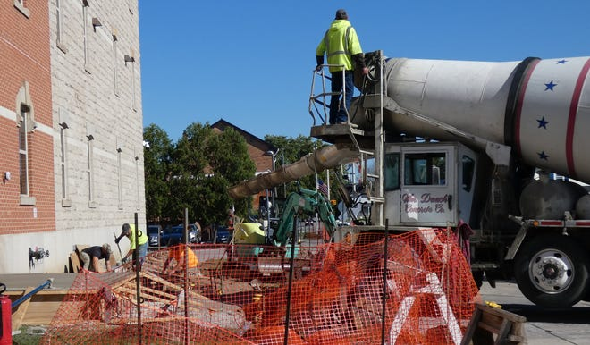 A crew from Studer-Obringer Construction Co. of New Washington installs a portion of a new concrete ramp leading to the Walnut Street entrance of the Crawford County Courthouse on Friday morning.The previous ramp was too steep to meet Americans with Disabilities Act guidelines, county officials said previously. The cement truck is from Wm. Dauch Concrete Co. of Norwalk.