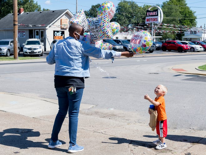 Melissa Moorehead Moore, left, hands a ballon to three-year-old Joseph Durham as she hosts a popup vaccine clinic for her 50th birthday at the Going Forward Beauty Salon in Evansville, Ind., Thursday afternoon, Sept. 23, 2021.
