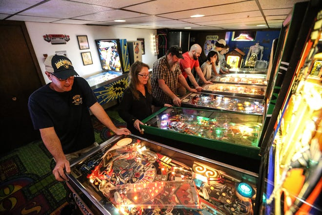 Kirk and Susan Hamer, Darrell Benson, Vincent Paul, Melanie Huff, Jack McDowell and Hunter Hamer play on Kirk's pinball game collection  at his home in North Fond du Lac. The iconic game has been experiencing a resurgence in recent years.