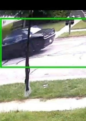 The black car pictured here was captured by a home surveillance camera in Benjamin Crossing at the time of Thursday's shooting. It matches the description of the suspect's car, according to police.