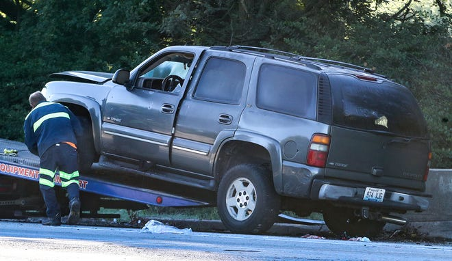 An SUV is loaded onto a wrecker on I264 East on Friday morning, September 24.  LMPD reports that the driver was shot and killed when exchanging gunfire with another vehicle and then crashed into the outside wall.