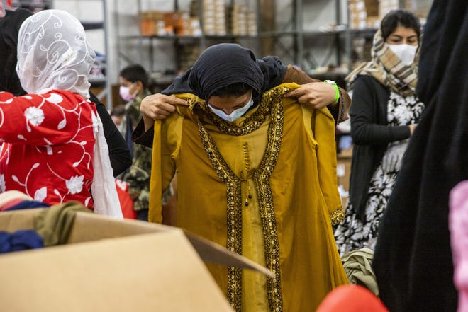 Afghan evacuees search for items at the clothing donation center on Fort McCoy as part of Operation Allies Welcome. Clothing donations have come from all around the Midwest to help Afghan evacuees, as many arrived at Fort McCoy with only one set of clothing.