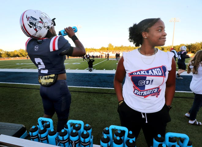 One of the Oakland High School football managers Divine McClay stands on the sidelines before the start of the game between Oakland and Lipscomb Academy as Oakland's running back Jordan James (2) drinks some water during warm-up before the game on Thursday, Sept. 23, 2021.