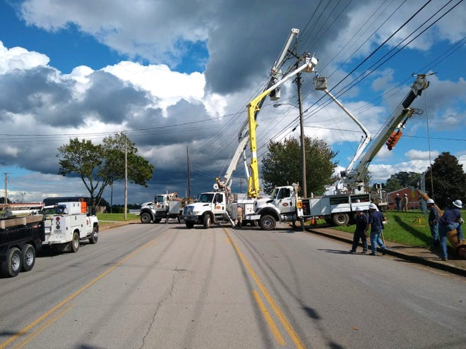 Dickson Electric System crews work to repair a power pole that caught fire near the funeral for Trooper Aaron Rumford on Wednesday. The crew worked to restore power to Walnut Street Church of Christ, the site of the funeral.