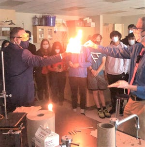 U.S. Secretary of Education Miguel Cardona participates in a chemistry experiment with Plymouth High School teacher Scott Milam.