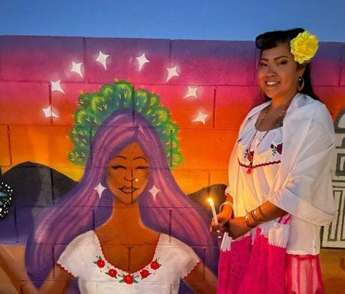 """Anitra """"Yukue"""" Molina poses next to her mural with a candle illuminating the wall."""