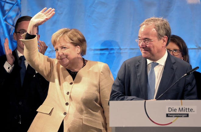 Armin Laschet, President of the German Christian Democratic Union (CDU) and the party's top candidate for federal elections, right, and German Chancellor Angela Merkel attend a joint campaign appearance in Stralsund, Germany, Tuesday, September 21, 2021. (Bernd Wustneck/dpa via AP)