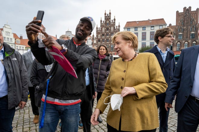 German Chancellor Angela Merkel, front right, poses for a picture with a visitor at the weekly market in    her former constituency in Marlow, Germany, Thursday, September 23, 2021. The outgoing chancellor had come to the German state of Mecklenburg-West Pomerania for a surprise visit.  (Stefan Sauer/dpa via AP)