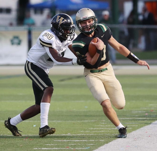 St. Vincent-St. Mary quarterback Nathan Lenz, right, is pushed out of bounds by Warren Harding's Davontae McElroy during the first quarter of their game at STVM on Friday night. Warren Harding won 20-17. [Karen Schiely/Beacon Journal]