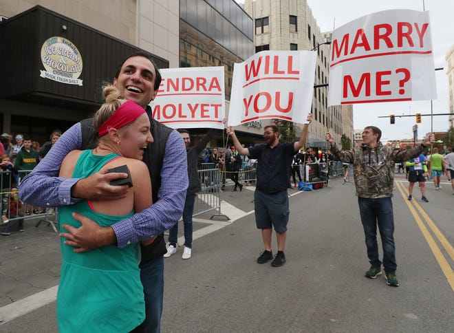 Kendra Molyet hugs Matt Smartnick after he proposed to her Saturday at the finish line of the Akron Half Marathon.