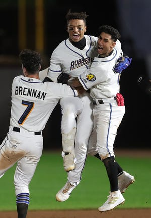 RubberDucks catcher Bo Naylor (12) celebrates with outfielder Will Brennan (7) and infielder Brayan Rocchio (9) after a walk-off win over the Bowie Baysox to win the Class AA Northeast Championship at Canal Park on Friday night. [Jeff Lange/Beacon Journal]