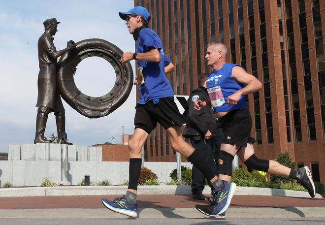 Runners race past the Rubber Worker Statue on Main Street in downtown Akron during the Akron Marathon on Saturday.