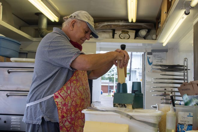Ron Puglisi shreds parmesan cheese for his pizza vending business at the Ashland County Fair.