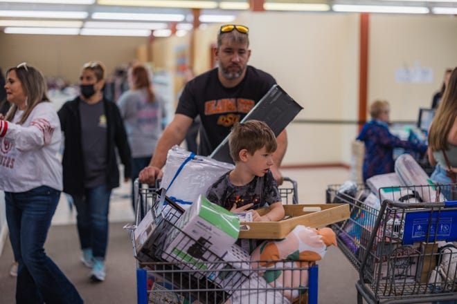 Customers fill shopping carts full of overstock items from stores like Target and online retailers like Amazon at the grand opening of $5 Gold Diggers on Saturday, Sept. 25 in Bartlesville.