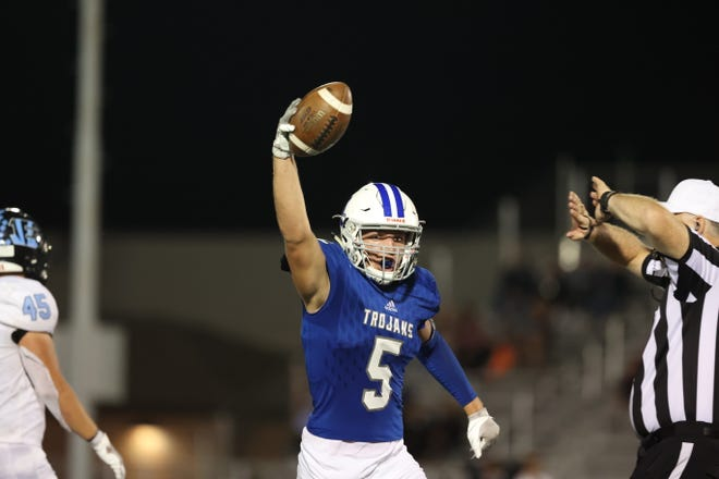 Andover Trojan's Matt Rudy (5) holds up a fumble he recovered in the third quarter against Goddard Eisenhower on Friday, Sept. 24 at Trojan Stadium.