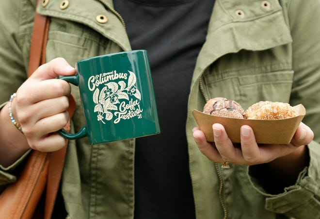 Stephanie Castine, of Vassar Village on the South Side, balances a mug of coffee and a portion of donuts during the 6th Columbus Coffee Festival at the Ohio History Connection's Ohio Village on Saturday.