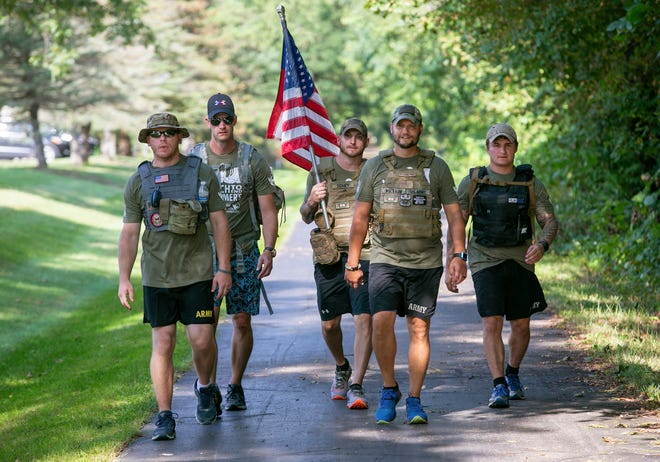 From left, veterans Cody Dilyard, Adam Hartle, Scott Doney, Tim Welbaum and Joshuah Sandlin walk the Kiwanis Trail in Adrian Friday afternoon as they make their way from Ann Arbor during a 34.5-mile trek raising awareness of Alzheimer's disease and the Alzheimer's Association.