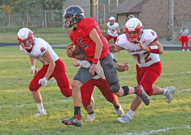 The Coldwater defense, led by Logan Farmer (72) and a host of other Cardinals, tackles Marshall's Nate Tucker Friday night