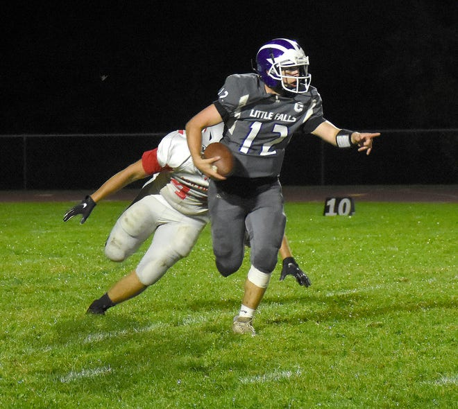 Little Falls quarterback Rikki Smith (12) directs his blockers Friday while running from Lowville Academy Red Raider Trent Nortz during the second half of a game played in Little Falls.