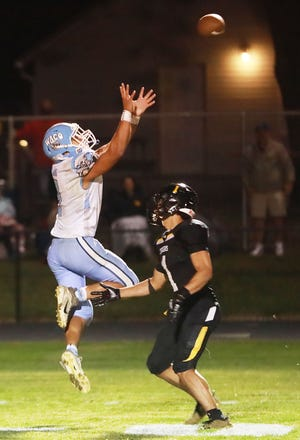 WACO's Jonah Clark leaps to make a pass reception over New London's Blaise Porter and would take it in to score the only touchdown of the game Friday at New London. WACO won, 7-0.