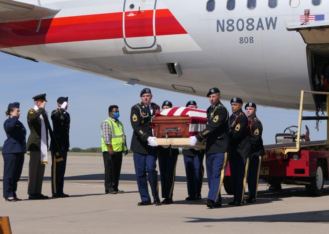 U.S. military pallbearers take The Rev. Emil Kapaun's casket off the airplane. His body traveled from Hawaii with Bishop Carl Kemme, of the Catholic Diocese of Wichita, and arrived at around noon Saturday at Wichita Dwight D. Eisenhower National Airport. At left, Kapaun's great niece, Christina Kapaun Roberts, salutes.