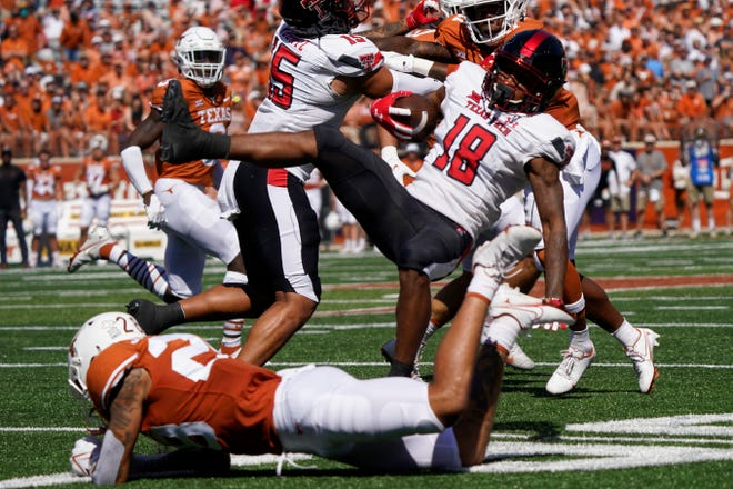 Texas Tech receiver Myles Price (18) is upended by Texas defensive back Christian Tschauner during the Red Raiders' 70-35 loss Saturday in a Big 12 opener at Royal-Memorial Stadium in Austin.