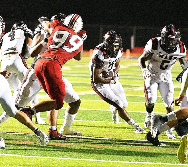 Running back Jeremiah James (with ball) breaks through a gap en route to a touchdown as he helped Many to a 46-7 win over Tioga on Friday night.