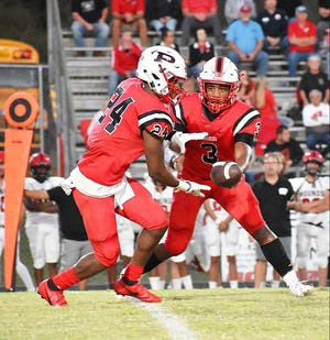 Pickering quarterback Marlon Freeney hands the ball off to Savion Adams during action Thursday at O'Banion Stadium. The Red Devils fell to Welsh, 57-14.