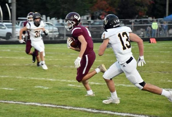 Charlevoix's Evan Solomon (6) makes a catch and turns up field against Glen Lake Friday night in Charlevoix.