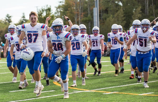 Seniors Cam MacHardy (87) and Zach Fredericks (88) lead the celebration after the Winnacunnet High School football team beat Exeter, 14-7 on Saturday afternoon.
