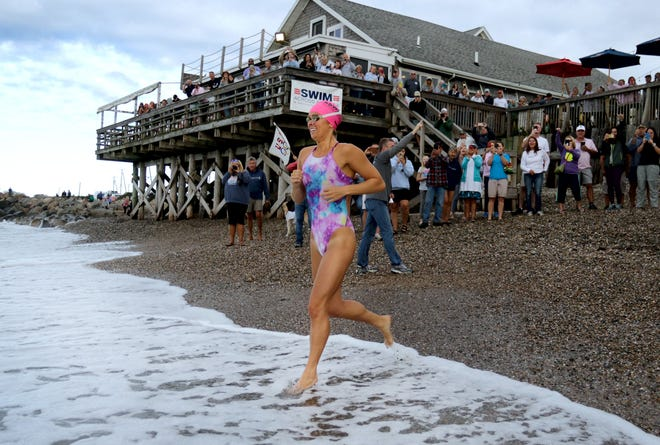 Olympic swimmer Elizabeth Beisel, cheered by family and supporters, runs into the ocean water on Saturday morning to start her South Kingstown to Block Island swim to raise money for cancer research.