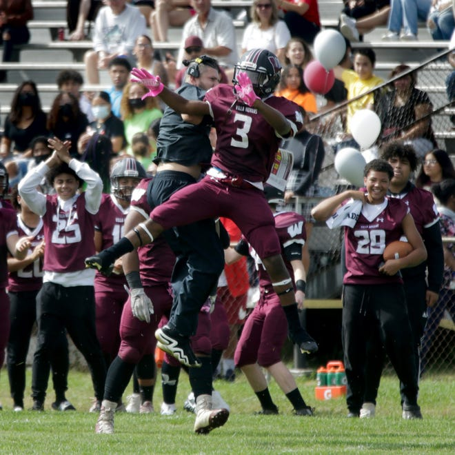 Woonsocket's Davonte Wilkerson celebrates with one of his coaches after his interception in the first quarter of Saturday's win over Cranston East in the Villa Novans' first game in almost two years.