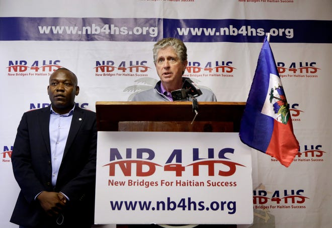 Gov. Dan McKee speaks about the plight of Haitian refugees at a news conference Saturday morning at the New Bridges for Haitian Success Inc. offices in Providence. To his left is the agency's founder, Bernard Georges.