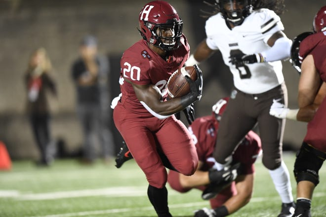 Harvard's Aaron Shampklin finds a hole in Brown's defense during Friday night's game at Harvard Stadium.