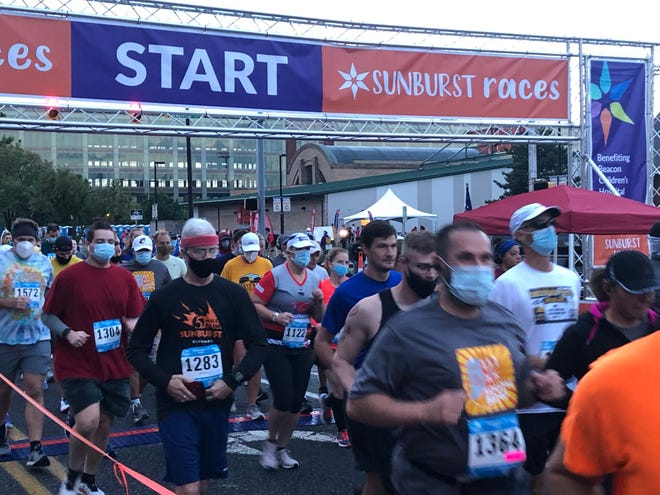Runners start this year's Sunburst 10K race Saturday morning on Lafayette Boulevard in downtown South Bend. They were required to begin with masks but could then toss them in barrels about 50 feet after the starting line. They were asked to put masks back on as they approached the finish line.